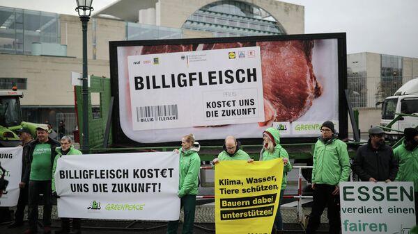 Активисты с плакатами Дешевое мясо стоит нам будущего в Берлине