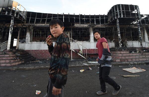 Молодежь проходит мимо сгоревшего здания в селе Масанчи в 250 километрах от Алматы 8 февраля 2020
