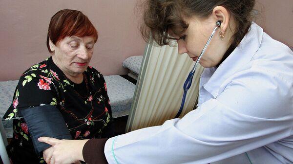Врач измеряет артериальное давление пациентке