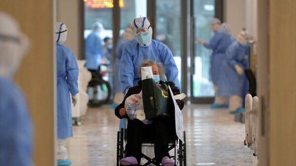 Медицинский работник в защитном костюме везет пациента с коронавирусом в больнице в городе Ухань, провинция Хубэй