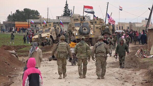 Военный конвой США и местные жители в районе города Эль-Камышлы в Сирии