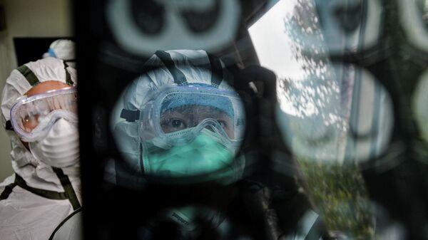 Медицинские работники в защитных костюмах изучают снимок КТ в медицинском центре в городе Ухань, провинция Хубэй