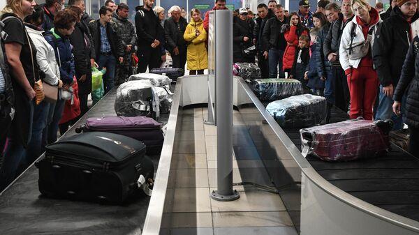 Пассажиры международных рейсов в зоне выдачи багажа