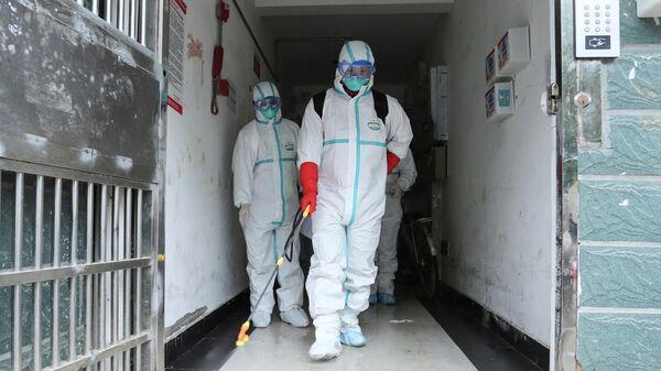 Cотрудники в защитной одежде дезинфицируют жилой район Ruichang в центральной провинции Цзянси, Китая