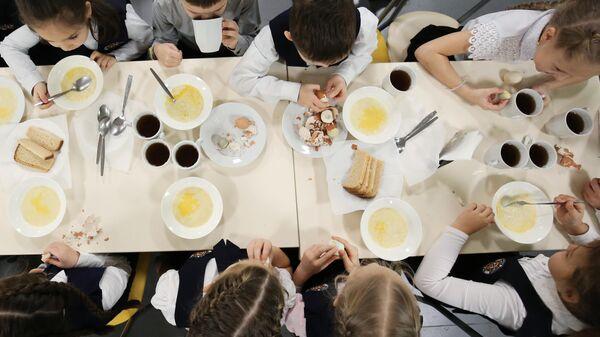 Ученики школы обедают в столовой