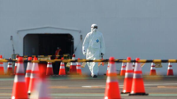 Мужчина в защитном костюме у круизного лайнера Diamond Princess в порту Йокогама