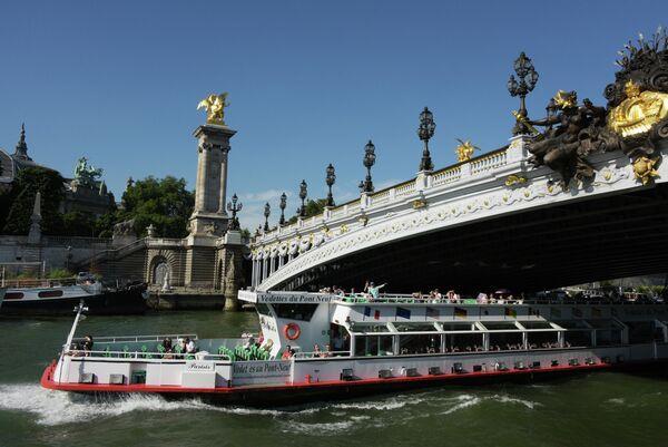 Туристический теплоход проходит под мостом Александра III в Париже