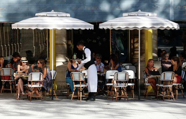 Посетители на летней веранде кафе возле Пале-Рояль в Париже