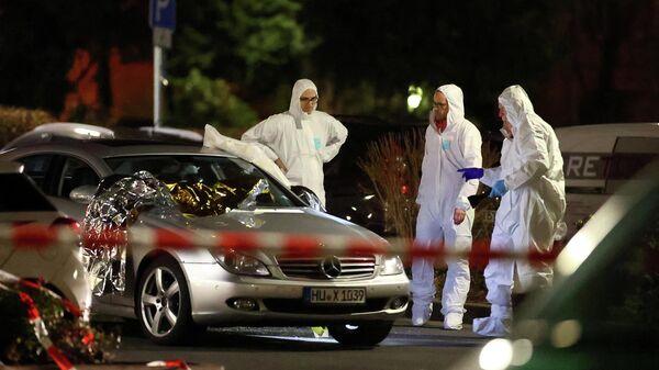 Судебные эксперты работают вокруг поврежденного автомобиля после стрельбы в Ханау под Франкфуртом, Германия. 20 февраля 2020