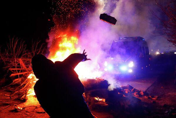Демонстрант бросает камень в сторону полицейского фургона во время акции протеста против прибытия самолета с эвакуированными из китайской провинции Хубэй в село Новые Санжары Полтавской области