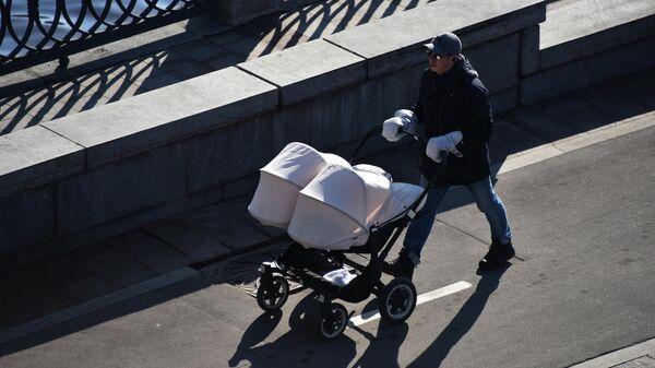 Мужчина с детской коляской идет по набережной