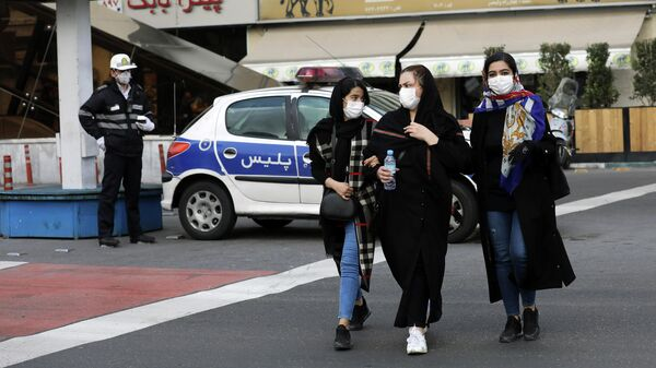 Люди в защитных масках на улице в Тегеране, Иран. 23 февраля 2020