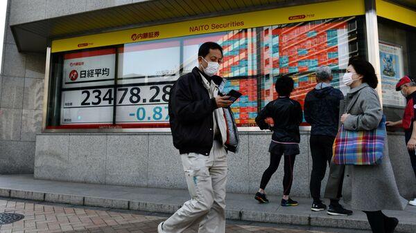 Прохожие проходят мимо табло Токийской фондовой биржи