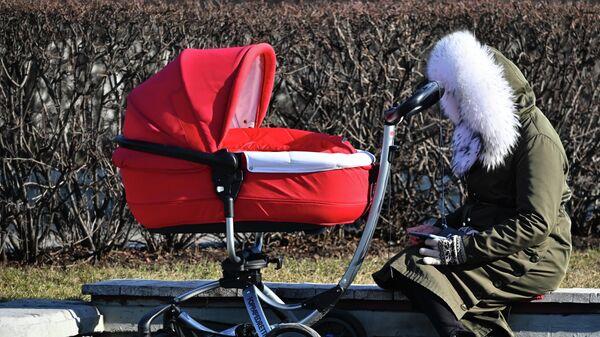 Женщина с детской коляской в парке