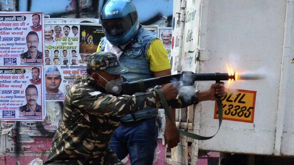 Полицейский во время столкновений в Нью-Дели