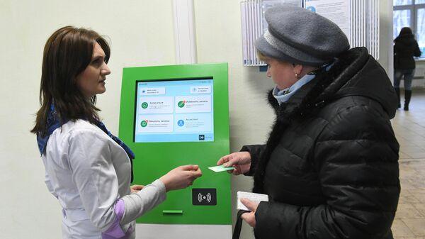 Пациент записывается на прием к врачу в шоу-руме поликлиники нового образца на территории диагностического центра №5 в Москве