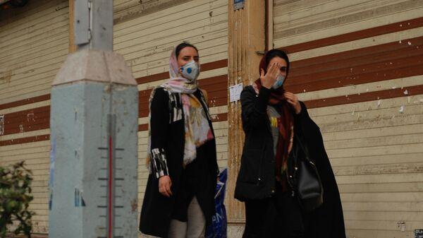 Люди в медицинских масках на улице столицы Ирана города Тегеран