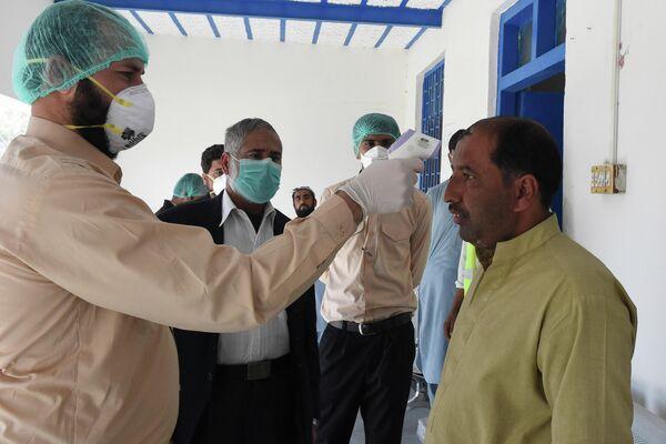 Врач проверяет температуру тела человека, возвращающегося из Ирана в карантинной зоне в пакистано-иранском приграничном городе Тафтан