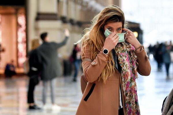 Девушка в медицинской маске на улице Милана