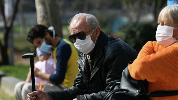 Люди, одетые в защитные маски, около больницы AHEPA