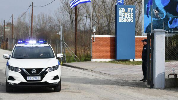 Автомобиль полиции у контрольно-пропускного пункта на границе Греции и Турции в районе поселка Кастанеэ