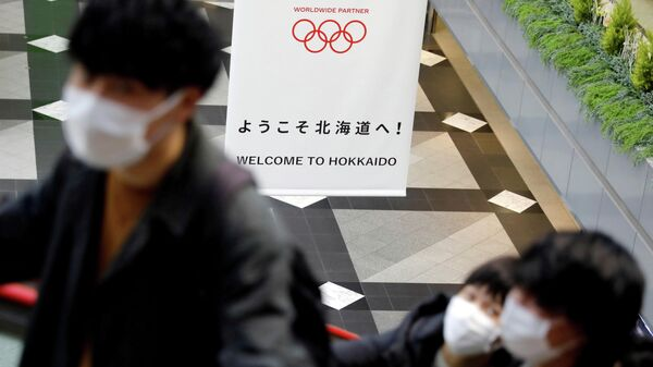 FILE PHOTO: Passengers wearing protective face masks, following an outbreak of the coronavirus, are seen near a campaign banner for Tokyo 2020 Olympic Games at New Chitose Airport in Chitose, Hokkaido, northern Japan February 27, 2020. REUTERS/Issei Kato/File Photo