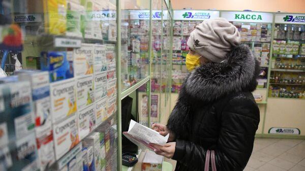 Покупательница в защитной маске в аптеке