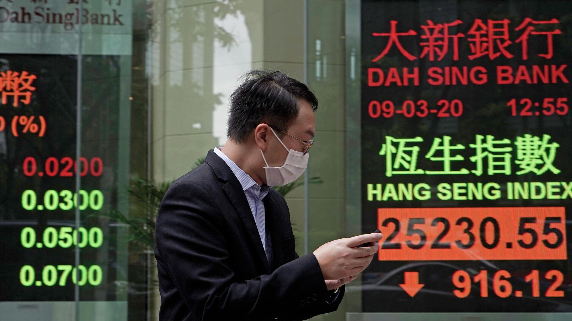Мужчина в защитной маске на фоне табло с котировками ценных бумаг в Гонконге  - РИА Новости, 1920, 17.09.2020