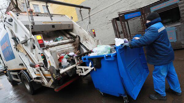 Выгрузка мусора из контейнера в мусоровоз