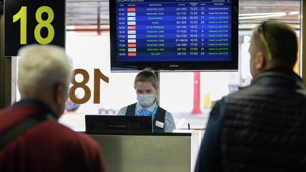 Сотрудница авиакомпании возле выхода на посадку в Международном аэропорту Сочи