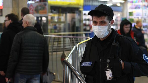 Сотрудник вневедомственной охраны в медицинской маске в Московском метрополитене