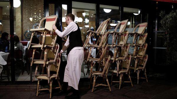 Сотрудник ресторана убирает стулья с террасы в связи с закрытием кафе и ресторанов в Париже