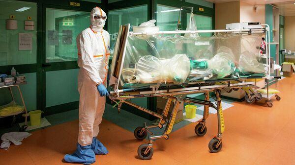 Медицинские работники в защитных костюмах транспортируют больного коронавирусом в больницу Коламбус Ковид, Италия