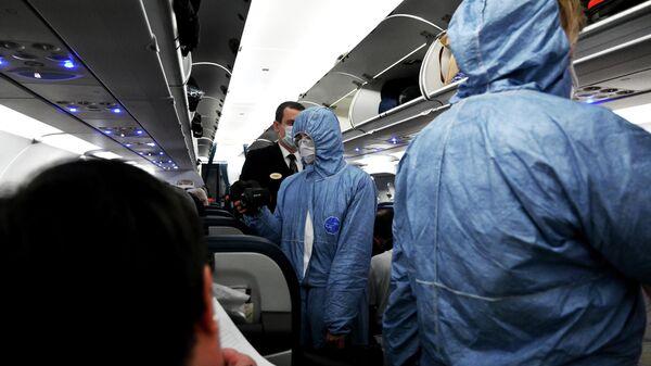 Сотрудники Роспотребнадзора измеряют температуру пассажиров на борту самолета в аэропорту Шереметьево