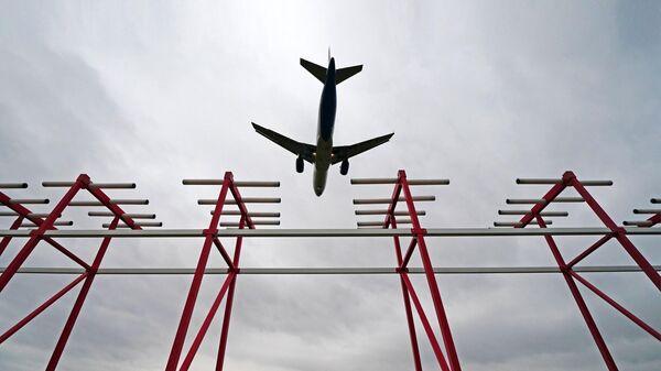 Самолет пролетает над курсовым радиомаяком системы посадки в аэропорту