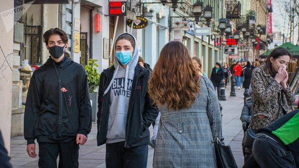 Прохожие в медицинских масках на улице Тбилиси