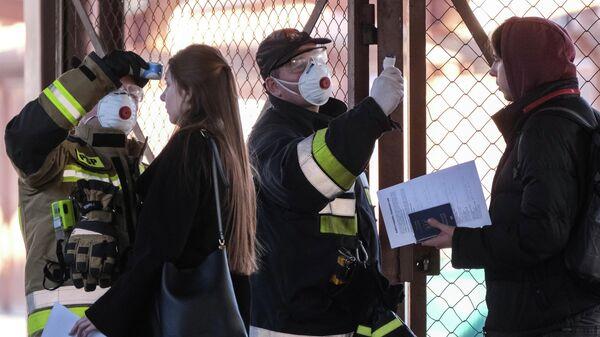 Польские сотрудники измеряют температуру тела пассажиров прибывших поездом из Украины на железнодорожном вокзале в Перемышле