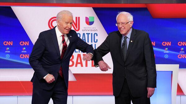 Кандидаты в президенты США Джо Байден и Берни Сандерс касаются друг друга локтями, вместо рукопожатия, перед началом предвыборных дебатов
