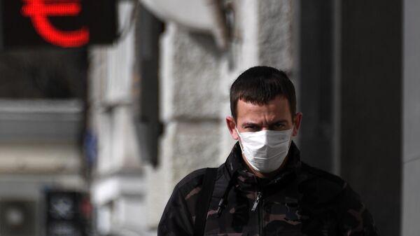 Человек в медицинской маске около электронного символа евро в Москве