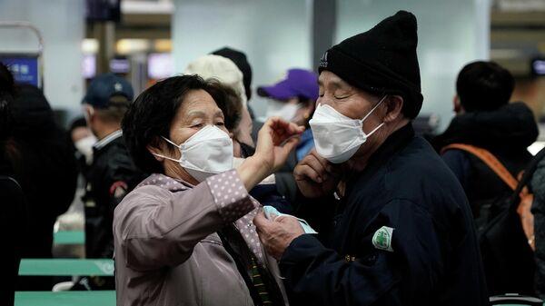 Мужчина и женщина ожидают начала регистрации в международном аэропорту Инчхон, Южная Корея
