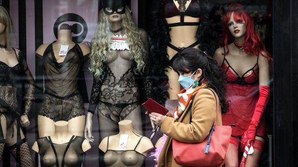 Женщина в медицинской маске проходит мимо витрины магазина в Париже
