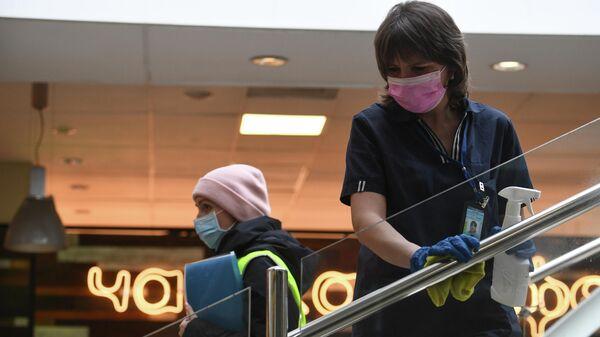 Сотрудница клининговой службы дезинфицирует поручни в аэропорту Толмачево в Новосибирске
