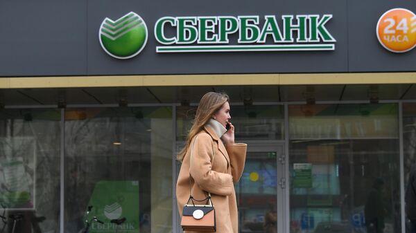 Девушка проходит мимо отделения ПАО Сбербанк на одной из улиц в Москве
