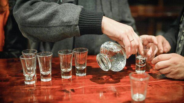 Посетитель разливает водку в пивном баре на Никольской улице в Москве