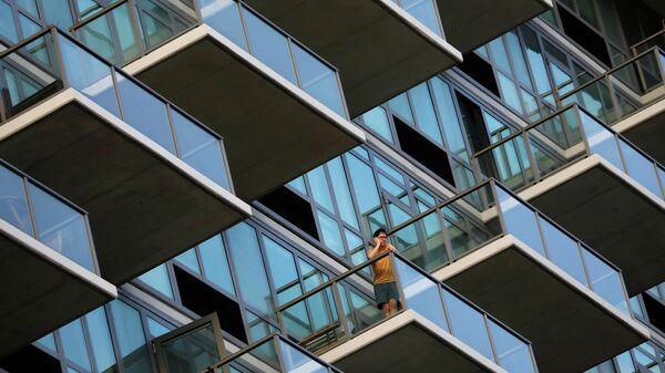Мужчина стоит на балконе многоквартирного дома в районе Квинс, Нью-Йорк, во время продолжающейся эпидемии коронавируса