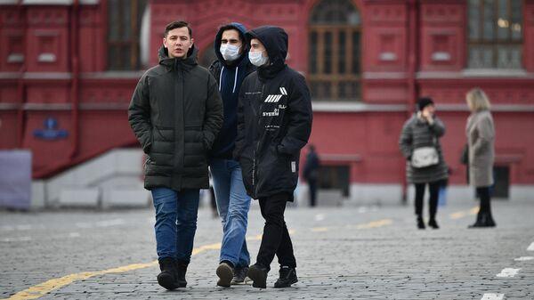 Прохожие в защитных масках на Красной площади в Москве