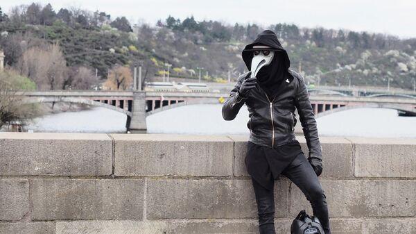 Мужчина в маске на опустевшей в связи с угрозой заражения вирусом COVID-19 улице Праги