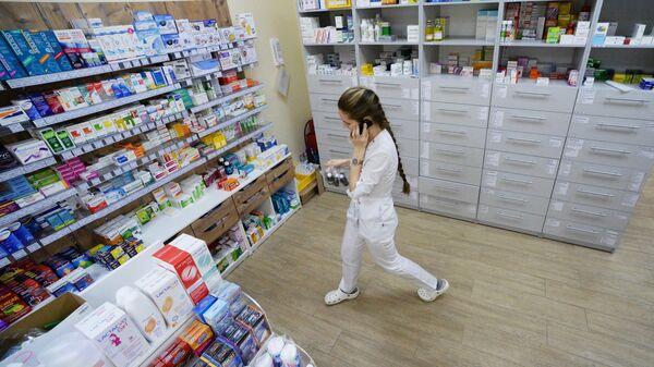 Фармацевт возле стеллажей с лекарствами в аптеке