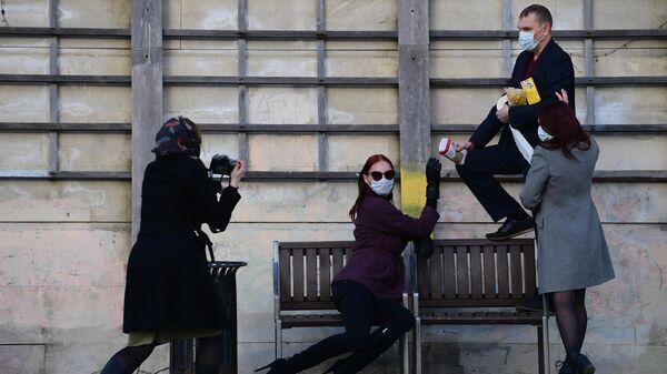 Молодые люди фотографируются на одной из улиц в Москве