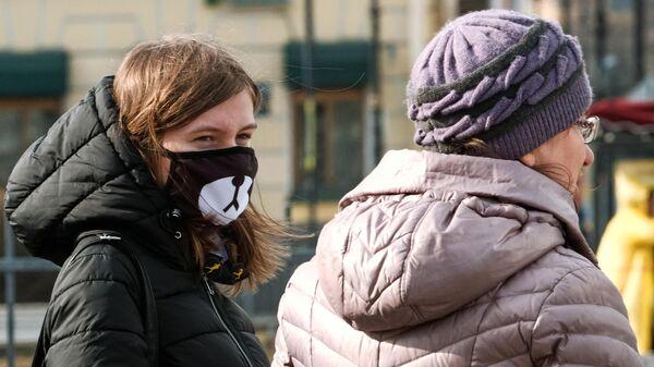 Прохожие в защитных масках на Невском проспекте в Санкт-Петербурге